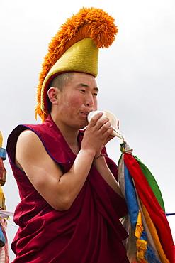 Buddhist monk blowing a conch shell by the Larviran Temple at the Erdene Zuu Monastery, Karakorum (Kharkhorin), Övörkhangai Province, Mongolia