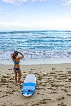 Young female surfer prepares on the beach to go out to the water, Honolulu, Oahu, Hawaii, United States of America