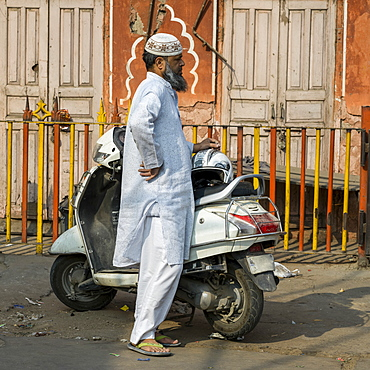 A man in traditional Indian dress stands on the street beside his motorcycle, Jaipur, Rajasthan, India