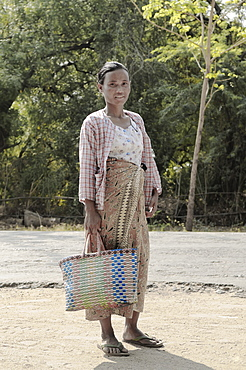 A woman standing with a woven bag going to market, Bagan, Myanmar