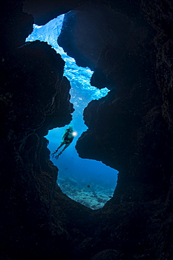 A diver (MR) shines her light into a crevice opening off Kaiwe Point on the Kona coast, Island of Hawaii, Hawaii, United States of America