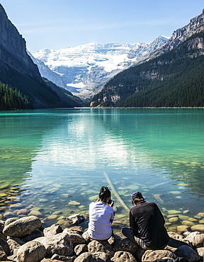 Two people distracted by looking at their smart phones while sitting along the shoreline of Lake Louise, Alberta Canada