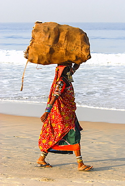 Karnataka woman walking on the beach carrying a bundle on her head, Goa, India