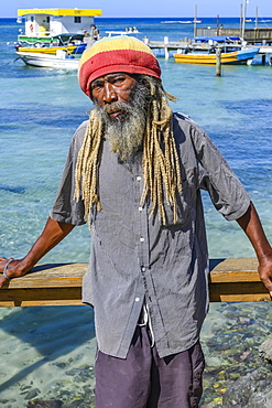 A man stands along the water's edge posing for the camera with boats moored at the dock in the background, depicting the people and lifestyle on the island of Roatan, West End Village, Roatan, Bay Islands Department, Honduras