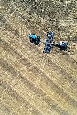Aerial view of air seeder in field, near Beiseker, Alberta, Canada
