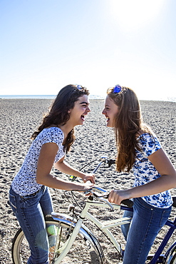 Two teenage girls being silly with a bike on Woodbine Beach, Toronto, Ontario, Canada