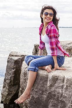 Teenage girl sitting on rocks looking out at the lake, Woodbine Beach, Toronto, Ontario, Canada