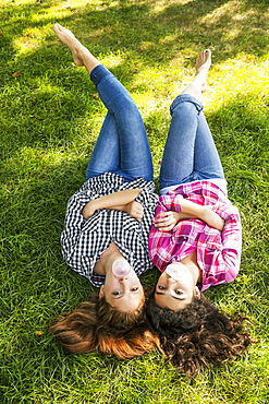 Two friends laying side by side on the grass blowing bubbles with bubblegum, Toronto, Ontario, Canada