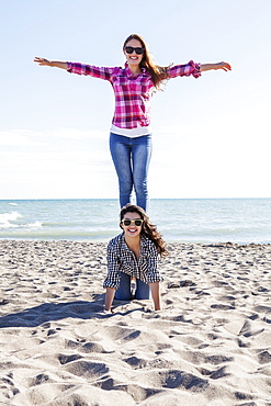 Two teenage girls posing while playing on the sand, Woodbine Beach, Toronto, Ontario, Canada