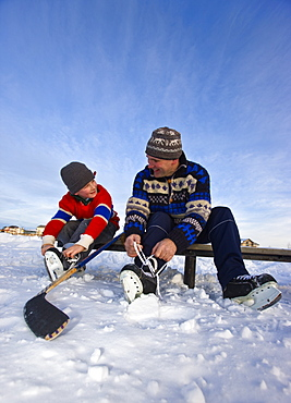 A father and son lacing their skates on a bench on a frozen lake for an outdoor hockey game, Alberta, Canada