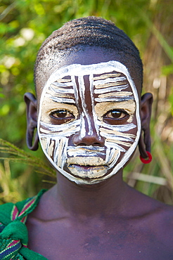 Surma girl with body paintings and distorted ears, Kibish, Omo River Valley, Ethiopia