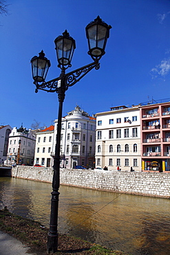 Ornate lamp post and buildings on bank of Miljacka River, Sarajevo, Bosnia and Herzegovina, Europe