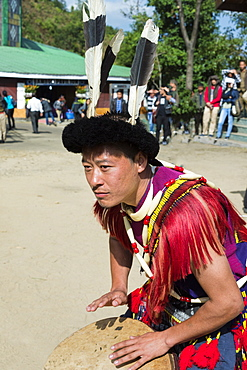 Naga tribal man in traditional outfit playing drum, Kisima Nagaland Hornbill festival, Kohima, Nagaland, India, Asia