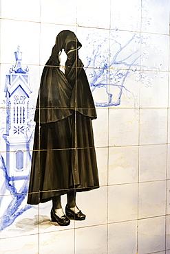Azulejos representing a Portuguese woman wearing a dark cape, Olhao, Algarve, Portugal, Europe
