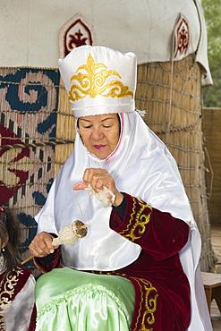 Kazakh woman spinning wool, Kazakh ethnographical village Aul Gunny, Talgar city, Almaty, Kazakhstan, Central Asia, Asia