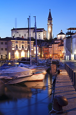 Waterfront buildings at the harbour and bell tower of Cathedral of St.George, Piran, Istria, Slovenia, Europe