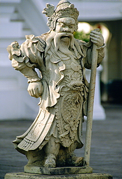 An ancient stone statue of a man dressed in long robes holding a staff outside the Grand Palace, Bangkok, Thailand.