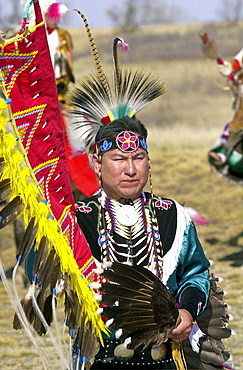 CANADIAN PLAINS INDIAN IN TRADITIONAL COSTUME AND FEATHER HEAD-DRESS AND CARRYING A FEATHER FAN AT WANUSKEWIN HERITAGE PARK, SASKATOON , CANADA.