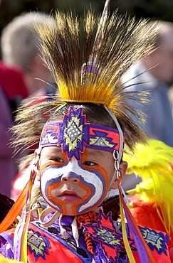 Cree Indian child, First Nation Canadian, in traditional costume with face painted at heritage display in Regina, Canada