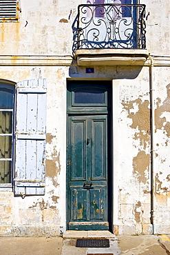 Traditional door on a run-down exterior, Ile De Re, France.