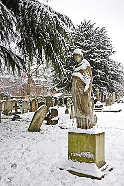 Snow covered monument and gravestones in Hampstead Parish churchyard, London, United Kingdom
