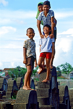 Young boys playing in a cemetery in Jakarta