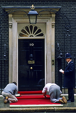 Policeman watches  red carpet being laid outside number 10 Downing Street, the home of the Prime Minister, London, UK.