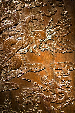 Qing Dynasty cabinet with engraved dragons and clouds design on display in the Shanghai Museum, China