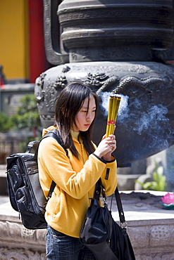 Worshipper burning incense at the Jade Buddha Temple, Shanghai, China