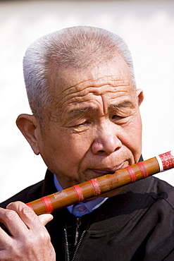 Man plays a Dizi flute in the park by the City Wall, Xian, China