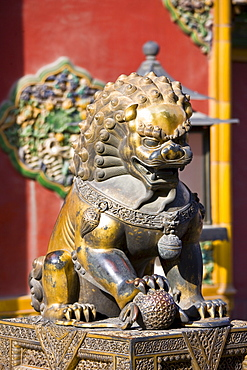 Gilded male lion statue with ball under paw in the Forbidden City, Beijing, China