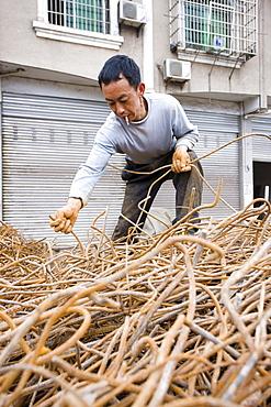 Man working at metal recycling steel in Dazu County, Chongqing, China
