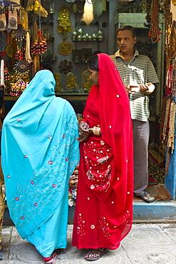 Indian women looking in shop window of jewellery shop in the city of Varanasi, Benares, Northern India
