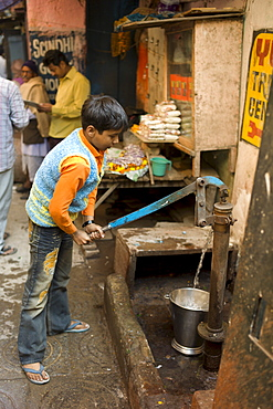 Indian boy using water pump in alleyway in the holy city of Varanasi, Benares, Northern India