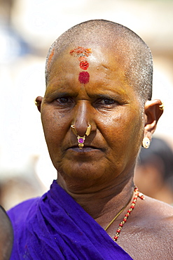 Hindu pilgrim woman with tilaka, bindi mark, nostril ring and yellow facepaint at Vishwanatha Temple (Birla Temple) during Festival of Shivaratri in holy city of Varanasi, India