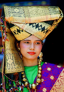 A young girl wearing an ornate gold head-dress with gold necklace and earrings in traditional style in Java, Indonesia.