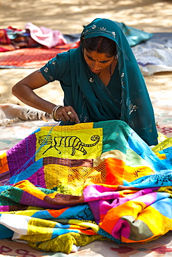 Indian woman sewing textiles at Dastkar women's craft co-operative, the Ranthambore Artisan Project, in Rajasthan, Northern India