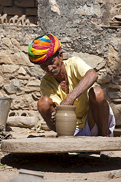 Indian potter in traditional Rajasthani turban works on potter's wheel at home making clay pots in Nimaj village, Rajasthan, Northern India