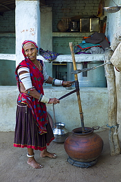Indian woman making buttermilk at home in Narlai village in Rajasthan, Northern India