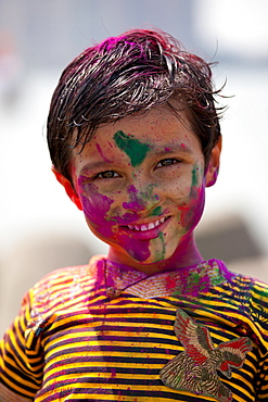 Young Indian boy celebrating annual Hindu Holi festival of colours with powder paints in Mumbai, formerly Bombay, Maharashtra, India