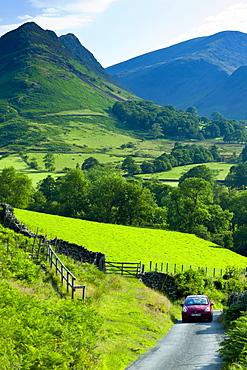 Motoring holiday tourists driving through Cumbrian mountain range near Derwentwater in Lake District National Park, UK