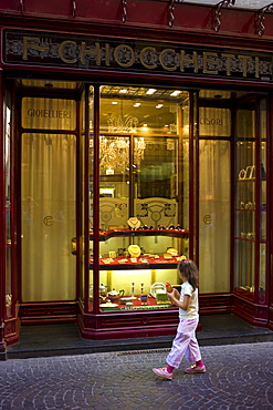 Young girl gazes at jewels in Fratelli Chiocchetti jewellery shop in Via Fillungo,  Lucca, Italy