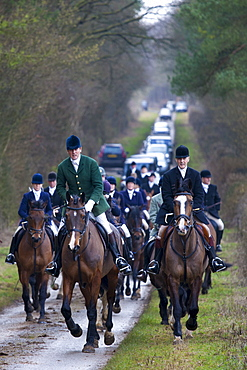 Members of the Heythrop Hunt, hunt official wearing green jacket, at a meet in Swinbrook in The Cotswolds, Oxfordshire, United Kingdom