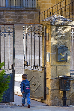 Young boy arrives at school in traditional Basque town of Laguardia in Rioja-Alavesa area of Spain