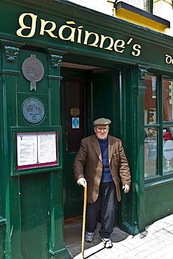 Elderly local Irishman with walking stick leaving Grainne's Bar in Mill Street, Timoleague, West Cork, Ireland