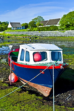 Brightly coloured fishing boat in the quay and thatched cottages  at Ballyvaughan, County Clare, West of Ireland
