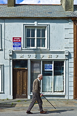 Old man strolls past Murphy shop with estate agent For Sale boards in, Kilkee, County Clare, West of Ireland