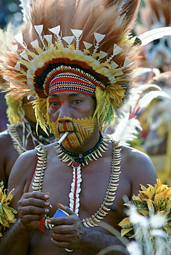 Tribesman smoking a cigarette while wearing face paints and feathered headdress during  a gathering of tribes at Mount Hagen in Papua New Guinea
