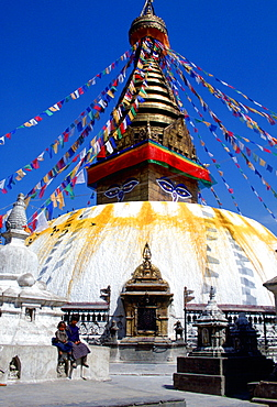 Children sitting on the wall outside theSwayambhunath Stupa  in Kathmandu valley in Nepal which is bedecked with flags.  It is a sacred monument in the Buddhist world and is a symbolic representation of the fully enlightened mind and the path to enlightenment.