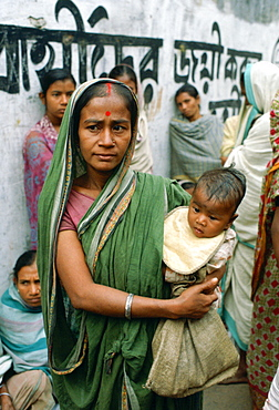 A mother carrying her child  and queuing for food handouts withother women at Mother Teresa's Mission in Calcutta,  India